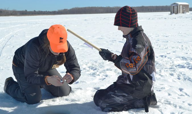 DNR  staff helping child ice fish   Lake Superior News